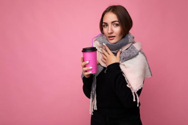 Привлекательная больная молодая брюнетка женщина в черном свитере и теплом шарфе на розовом фоне держит бумажную кофейную чашку для питья макета и смотрит в камеру