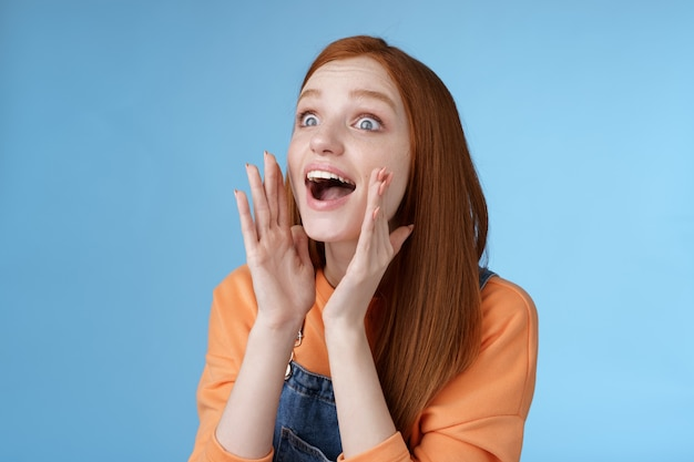 Attraente stupida rossa europea giovane ragazza 20 anni che chiama amico alla ricerca di qualcuno folla sembra rilassata urlando con gioia tenere le mani bocca aperta gridando nome più forte guarda a sinistra, sfondo blu.
