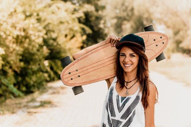 Attractive skater girl holding skateboard in her hands