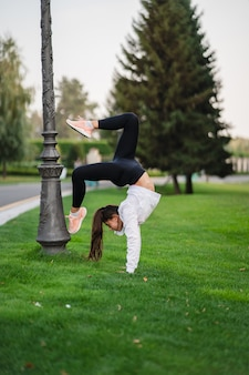 Attractive skinny woman doing a backbend while showing a somersault.
