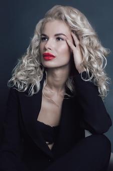Attractive slavic blonde woman dressed in total black posing on the dark studio