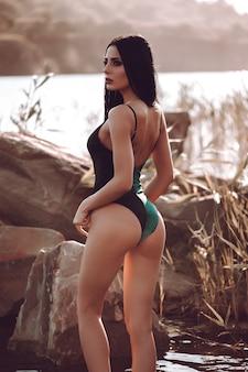 Attractive slender girl in green swimwear posing on white sand beach.