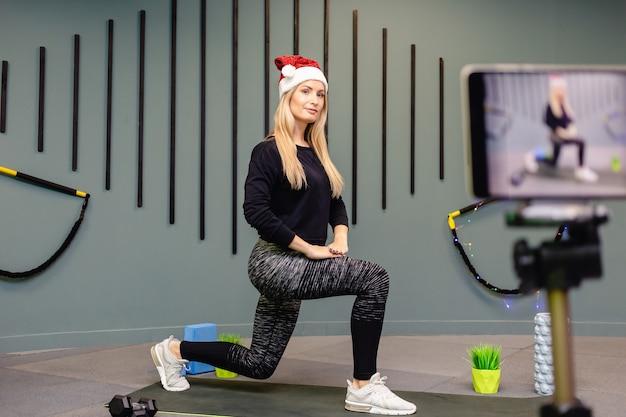 Привлекательная стройная девушка в шляпе санты занимается фитнесом и снимает себя на камеру. концепция онлайн-занятий, видеоурок