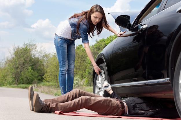 그녀의 차에서 작업하는 정비공을 돕는 매력적인 날씬한 젊은 여성 드라이버