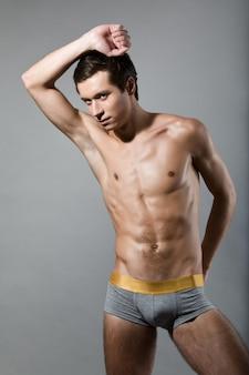 스튜디오에서 회색 배경에 포즈 회색 반바지를 입고 매력적인 슬림 젊은 스포츠 남자. 남성 상품 및 속옷 광고의 개념. 광고 공간