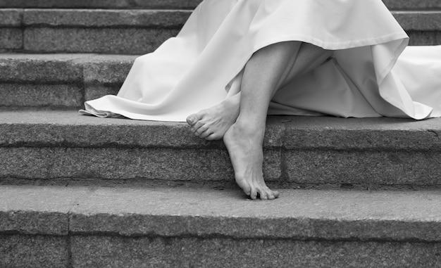 写真のドレスを着た若い女性の魅力的なスリムな裸足の脚と足