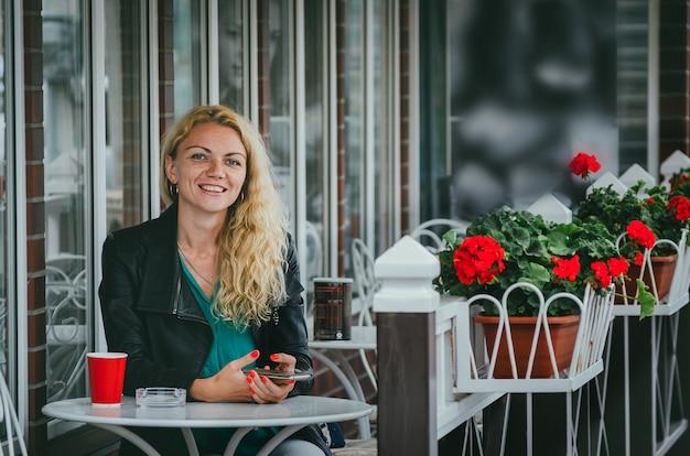 魅力的でスリムな金髪の女性は、マットレスにメッセージを書き、サマーテラスのカフェに座って、コーヒーを飲みます。フリーランサーの仕事、仕事の瞬間の決定。