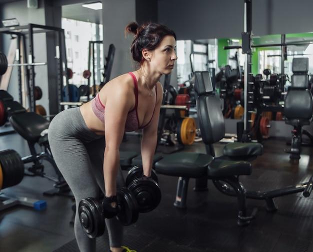 Привлекательная стройная женщина в спортивной одежде делает упражнение, подтягивая гантели к поясу, стоя на склоне в тренажерном зале.