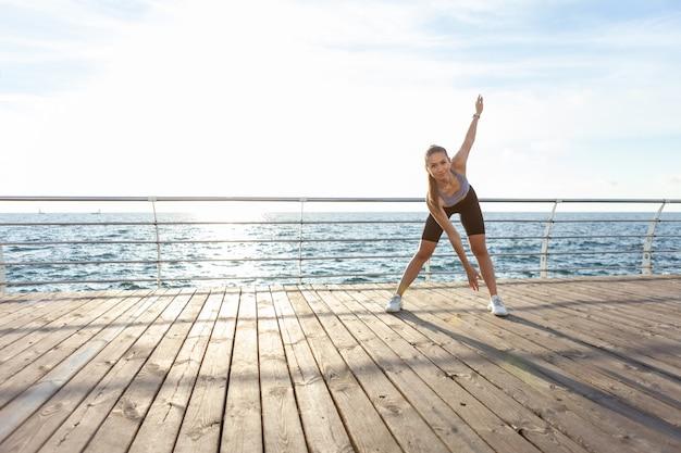 日の出のビーチでウォームアップエクササイズをしている魅力的なスリムフィットの若い女性