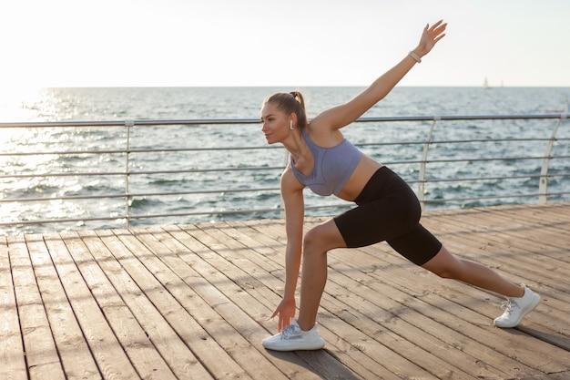 일출 때 해변에서 워밍업 운동을 하는 매력적인 날씬한 젊은 여성