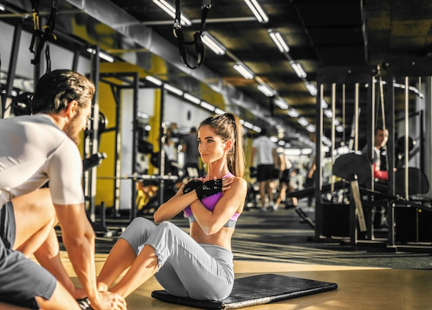 Attractive slim girl doing abs exercise on a black mat with crossed hands with her muscular personal trainer while holding her legs and looking each other in the modern gym.