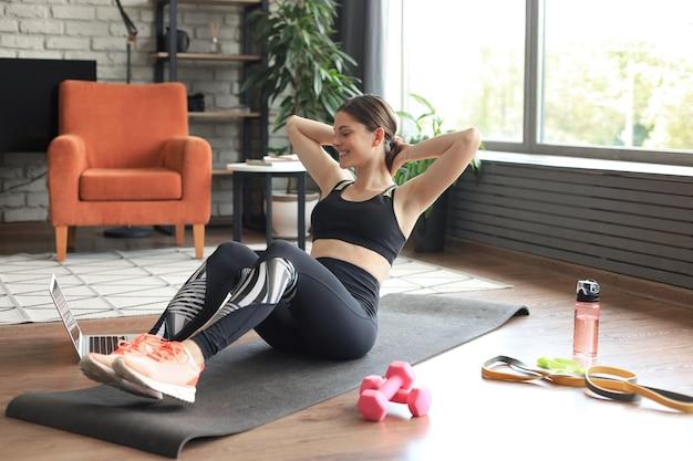 Привлекательная худенькая девушка в спортивной одежде делает упражнения на пресс на полу дома. здоровый образ жизни.