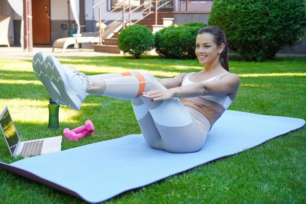 Привлекательная худенькая девушка в спортивной одежде делает упражнения на пресс на открытом воздухе. здоровый образ жизни.