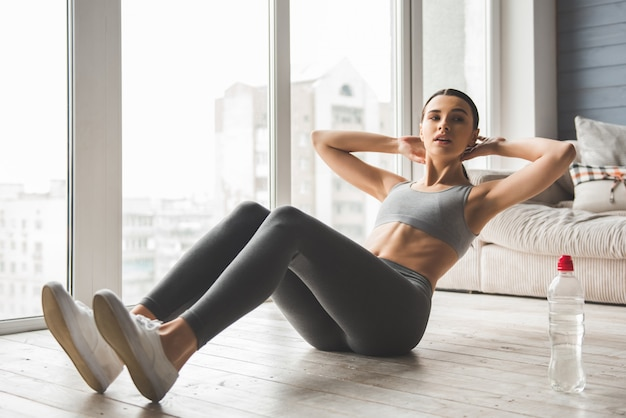 Attractive slim girl in sportswear is doing abs