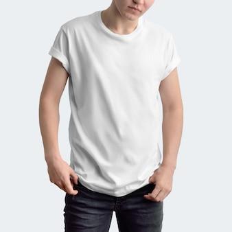 흰색 스튜디오 배경에 빈 티셔츠와 어두운 청바지를 입은 매력적인 날씬한 남자. 정면 포즈. 모형은 쇼케이스에서 사용할 수 있습니다.