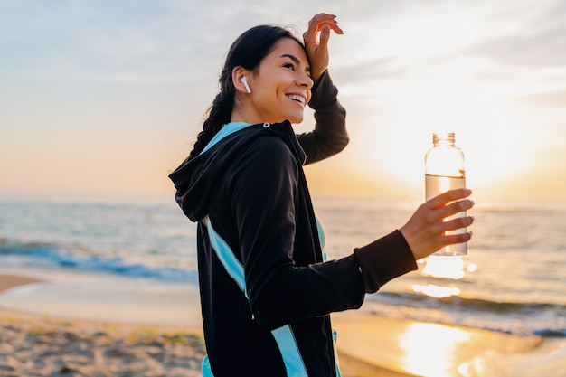 Attractive slim woman doing sport exercises on morning sunrise beach in sports wear, thirsty drinking water in bottle, healthy lifestyle, listening to music on wireless earphones, feeling hot