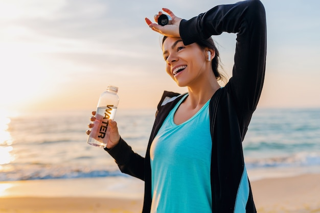 Attraente donna magra facendo esercizi sportivi sulla spiaggia di alba mattutina in abbigliamento sportivo, acqua potabile assetata in bottiglia, stile di vita sano, ascolto di musica con auricolari wireless, calda giornata estiva
