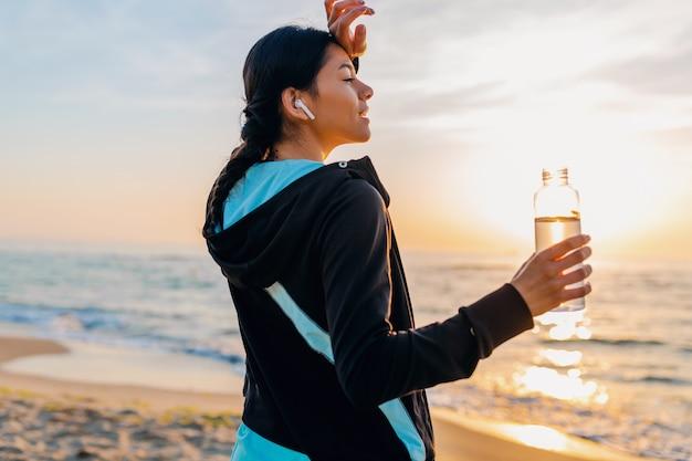 Attraente donna magra facendo esercizi sportivi sulla spiaggia all'alba del mattino in abbigliamento sportivo, acqua potabile assetata in bottiglia, stile di vita sano, ascolto di musica su auricolari wireless, sorridendo felice