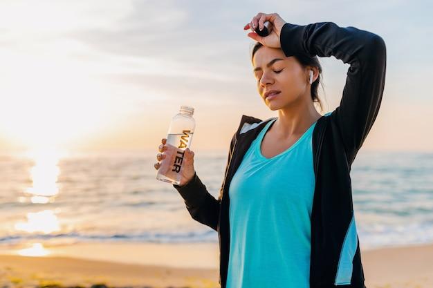 スポーツウェアの朝日ビーチでスポーツエクササイズをしている魅力的なスリムな女性、ボトルの喉が渇いた飲料水、健康的なライフスタイル、ワイヤレスイヤホンで音楽を聴いて、暑い夏の日