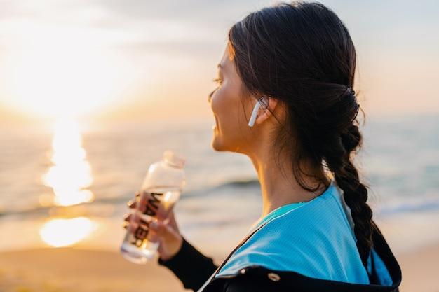スポーツウェアの朝の日の出のビーチでスポーツエクササイズをしている魅力的なスリムな女性、ボトルの喉が渇いた飲料水、健康的なライフスタイル、ワイヤレスイヤホンで音楽を聴いて、幸せな笑顔