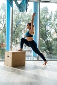 Привлекательная стройная женщина в спортивной одежде делает расслабляющие упражнения на деревянном кубе в тренажерном зале