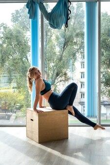운동복에 매력적인 슬림 여자는 체육관에서 나무 큐브에 운동을 이완