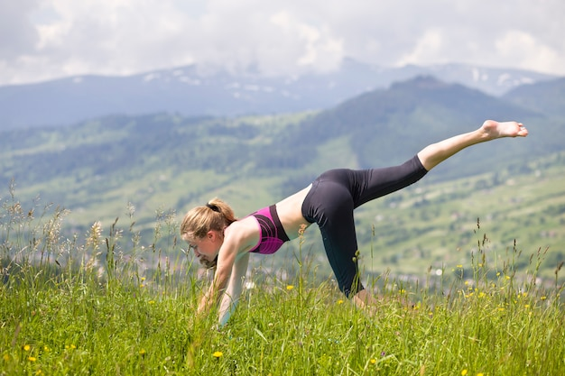 Attractive slim young woman doing yoga exercises outdoors