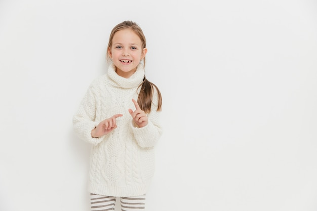 Attractive small female child in warm winter sweater, hears positive story from friend, stands against white