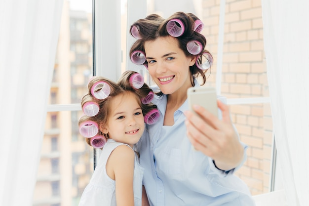 Attractive small kid with positive expression, charming smile stands near her mother
