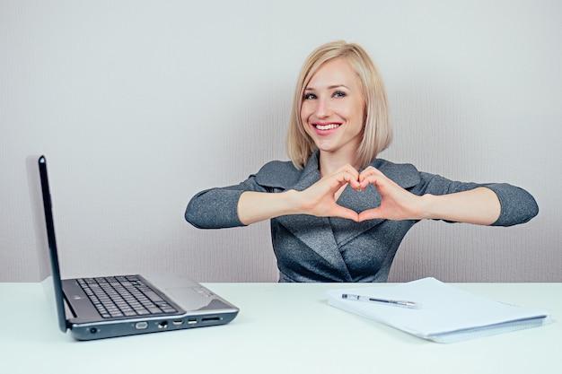 ラップトップとフォルダーの束で作業するスタイリッシュなスーツの魅力的なスマートブロンドマルチタスク女性(ビジネスレディ)は、オフィスで指を指しています。インスピレーションとアイデアの概念