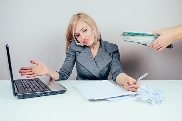 スタイリッシュなビジネススーツを着た魅力的なスマートブロンドマルチタスク女性秘書(ビジネスレディ)は、ラップトップでたくさんのフォルダを操作し、オフィスで電話で話します。ビジネスコンセプトと期限