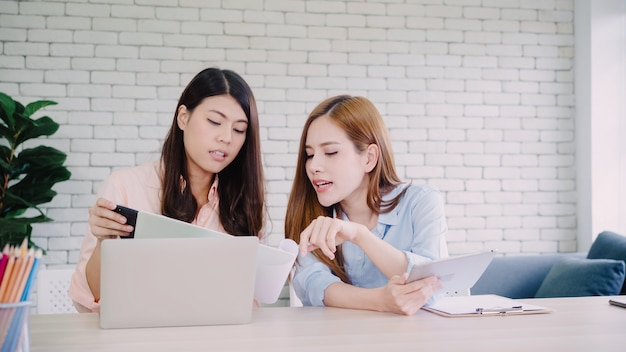 Attractive smart creative asian business women in smart casual wear working on laptop while sitting