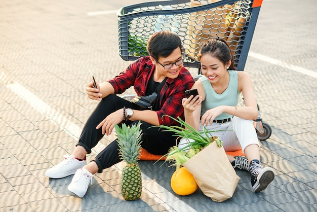 Attractive smiling 30s couple relaxing after shopping,sitting on the ground near big store and watching amusing pictures on their smartphones