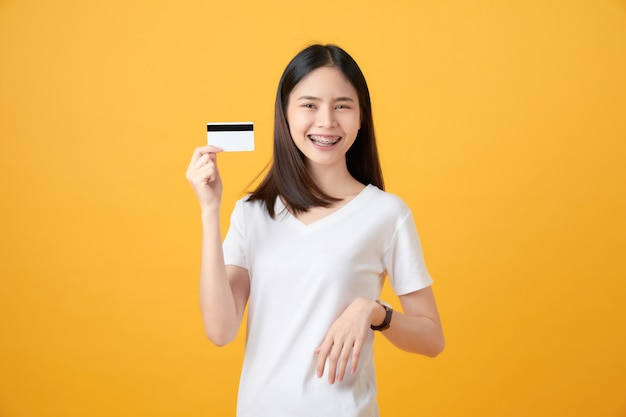 Attractive smiling asian woman holding credit card payment on yellow wall