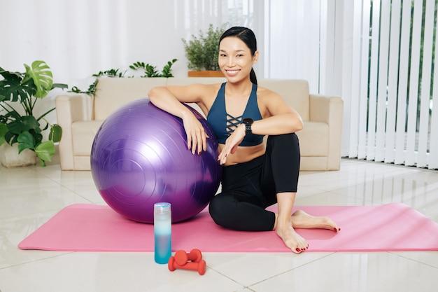Привлекательная улыбающаяся азиатская женщина, сидящая на коврике для йоги, опираясь на фитнес-мяч и улыбаясь в камеру