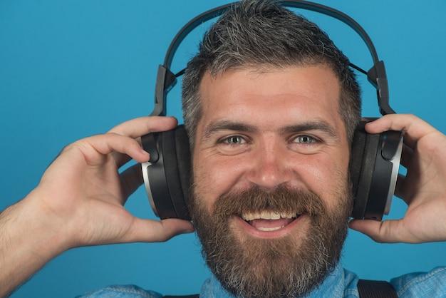헤드폰을 끼고 웃고 있는 매력적인 수염 난 남자가 좋아하는 노래를 즐기고 있는 행복한 세련된 남자