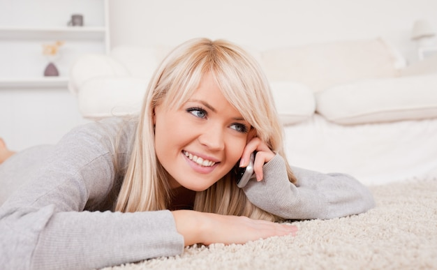 Attractive smiling blond woman talking on cell phone lying down on a carpet