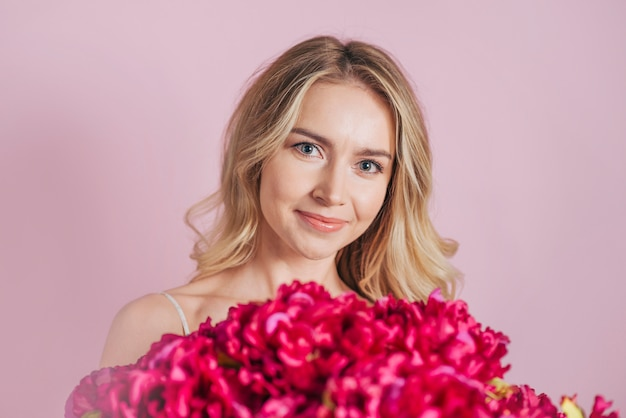 An attractive smiling blonde young woman with red flower bouquet against pink background
