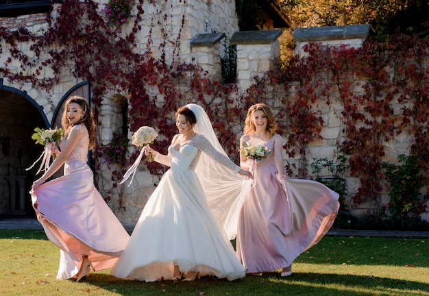 Attractive smiling bride and bridesmaids are dancing and having fun in front of stone building covered with red ivy