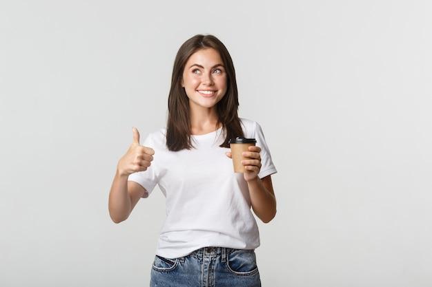 Привлекательная улыбающаяся брюнетка девушка выглядит довольной, пьет кофе и показывает палец вверх, рекомендую кафе.