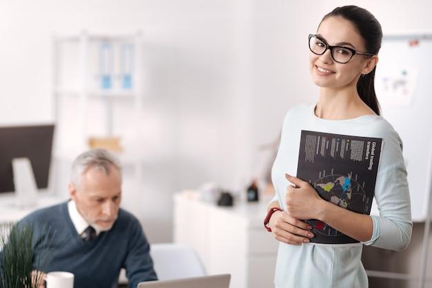 Привлекательная улыбающаяся брюнетка, стоящая в полу-положении в офисе, держа левую руку согнутой в локте, глядя прямо вперед