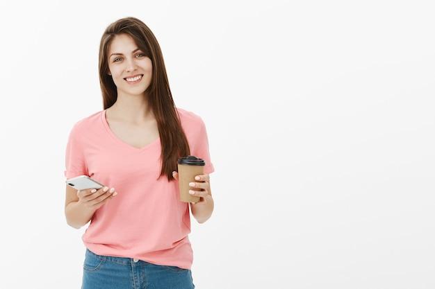 彼女の携帯電話とコーヒーとスタジオでポーズをとって魅力的な笑顔のブルネットの女性