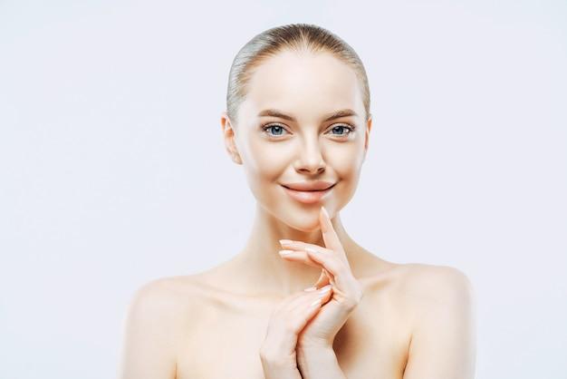 魅力的な笑顔のブルネットの女性は最小限の化粧を着ています。