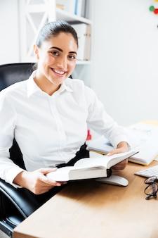Привлекательная улыбающаяся деловая женщина, читающая книгу, сидя на рабочем месте в офисе