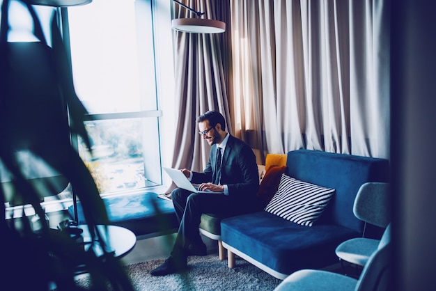 Attractive smiling caucasian bearded businessman in suit and with eyeglasses sitting in his office on couch next to window and using laptop.