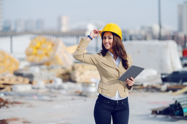 Attractive smiling caucasian female architect in beige jacket and with protective helmet on head standing on construction site, holding tablet and looking at camera.