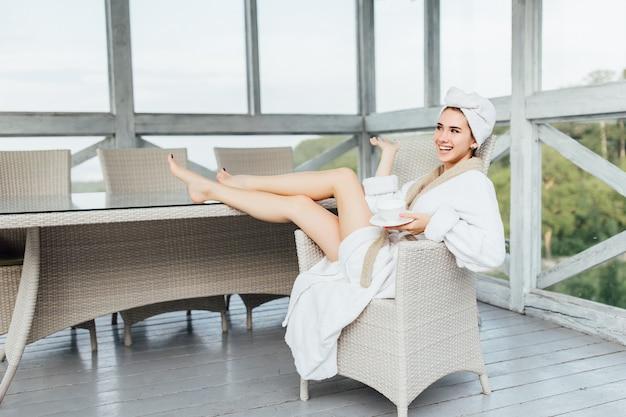 매력적인, 미소, 흰색 가운에 귀여운 소녀, 커피 한잔과 함께 호텔 테라스에 앉아.