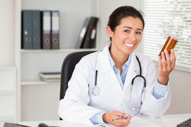 Привлекательный улыбающийся доктор, проведение коробки с таблетками