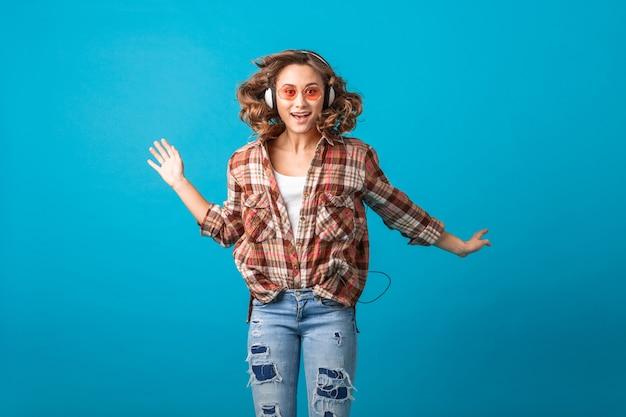 Attraente donna emotiva sorridente che salta con espressione divertente faccia pazza in camicia a scacchi e jeans isolati su sfondo blu studio, indossando occhiali da sole rosa