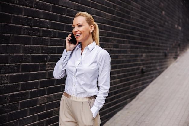 屋外を歩いて電話で話している魅力的な笑顔のファッショナブルな女性。